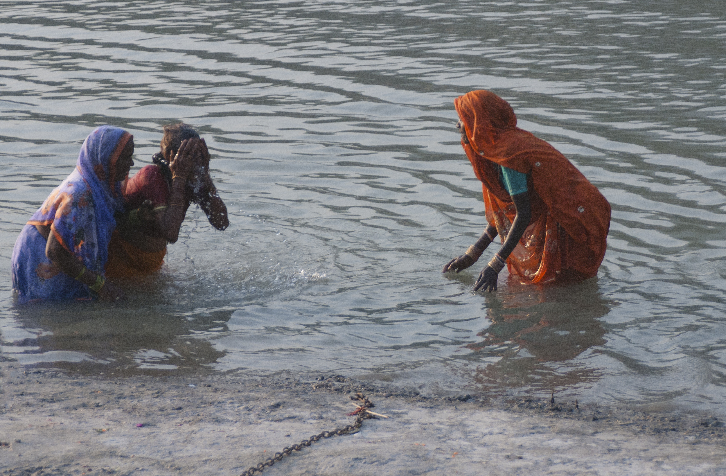 Woman practice ritualistic washing in the river. The chain can be attached to those who cannot swim to keep from drowning.