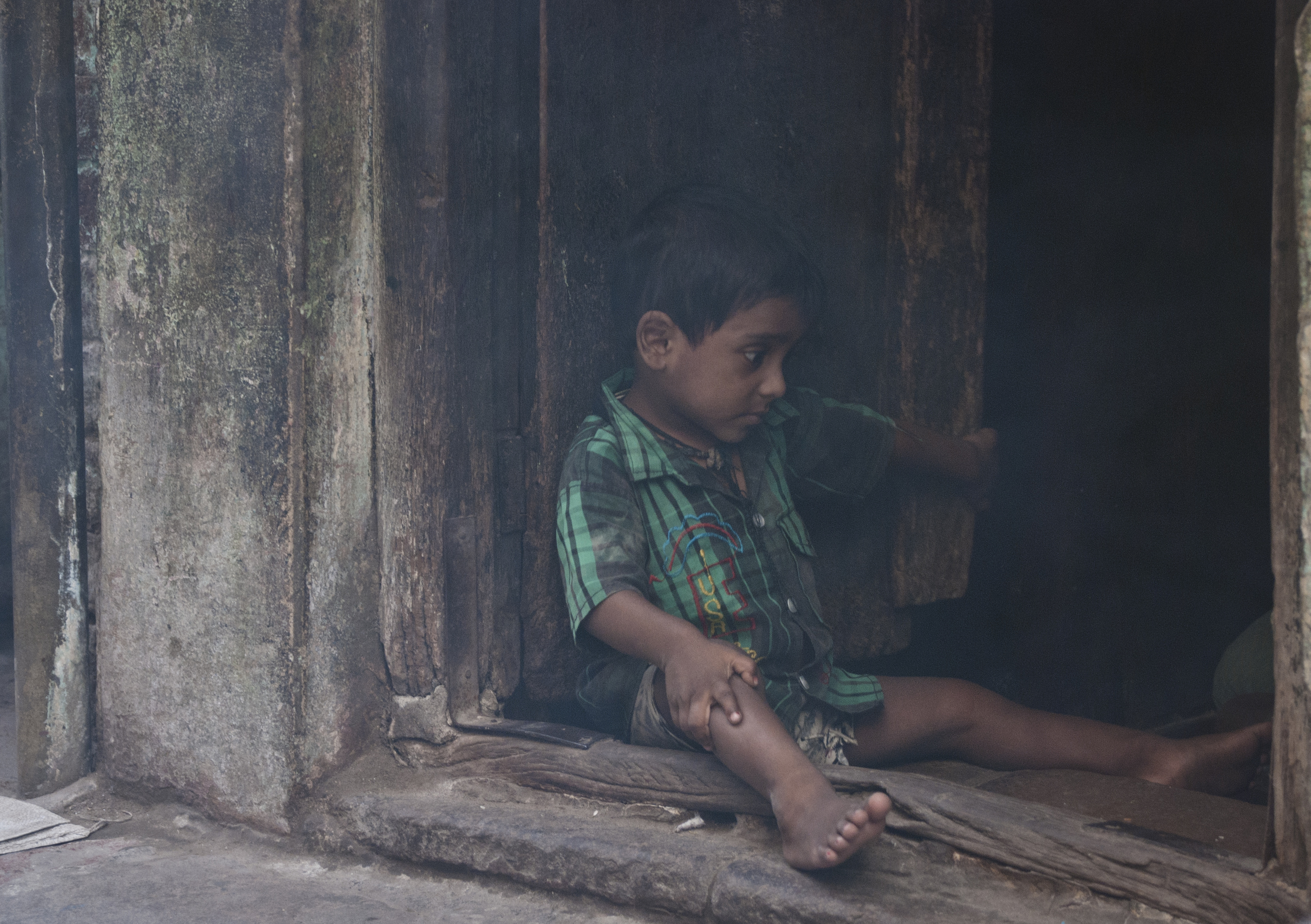 A child acting coy as he sits in the dust filed door way to his home.
