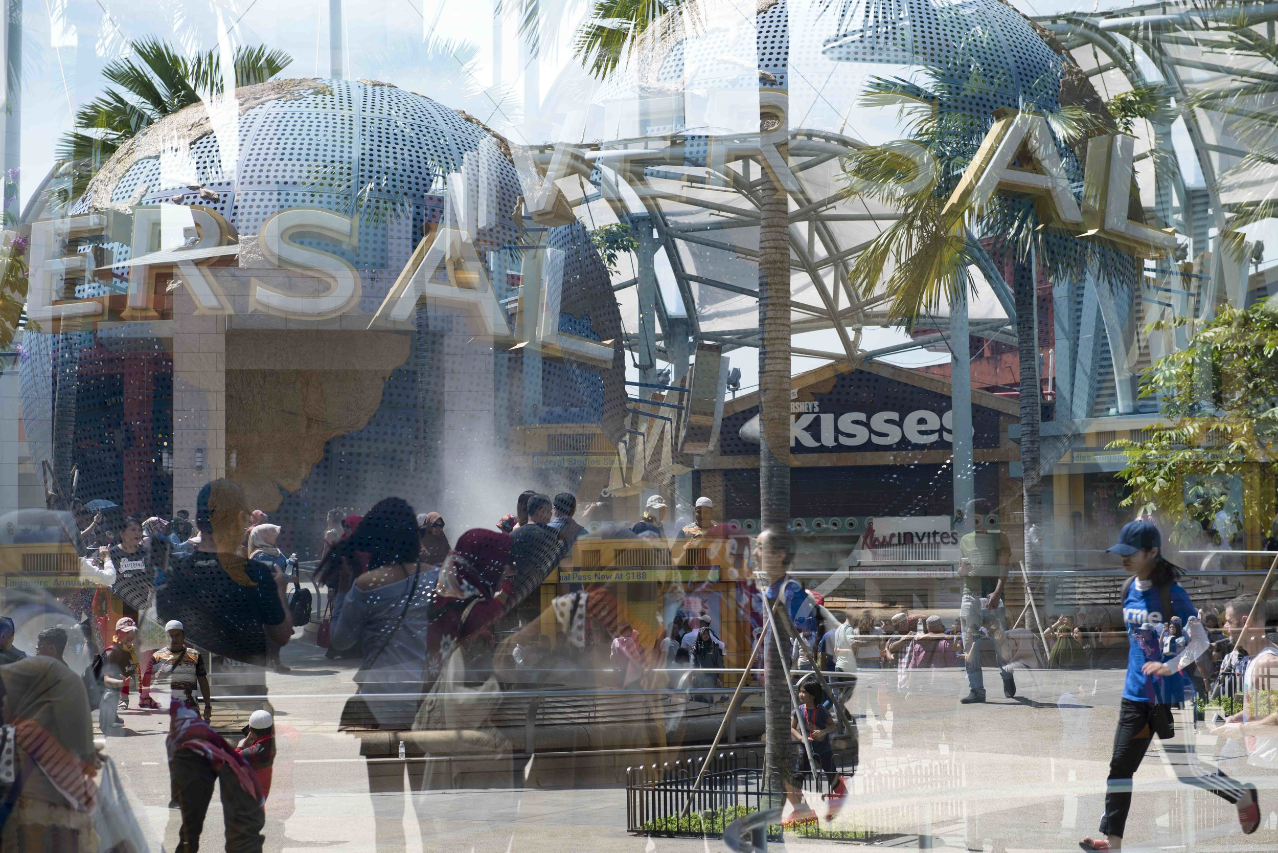 Double Exposure No:7 © Naida Ginnane 2018, Nikon D800, 24-70mm lens. 1/250 at f/6.3  We see two different views of the theme park entrance. Two different moments in time overlapping, gives us an impression of the crowd and busyness of the location.