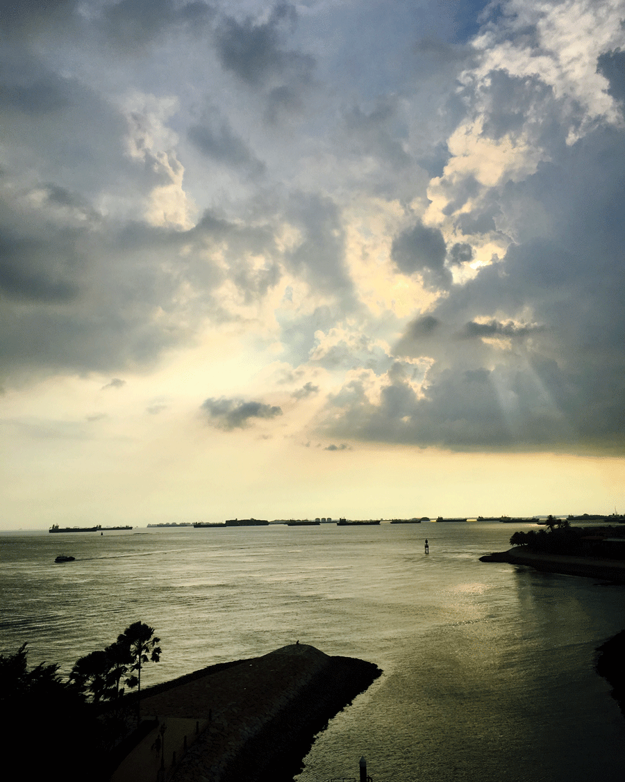 Sunset Singapore © Naida Ginnane 2018, iPhone 6  There are two types of leading lines in this image. The dark shapes of the land in the foreground direct the eye upwards, while the beams of light coming from the clouds continue the direction upward to the contrasting tones of the clouds.