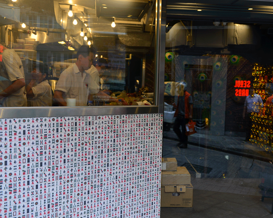 Dim Sum © Naida Ginnane 2016, Nikon D800, 24-70mm lens.  This image is broken up into three distinct areas. The tiles in front left, the window above showing the cooks working inside with reflections of lights on the glass, and the right panel which is a pane of glass reflecting the scene across the street.