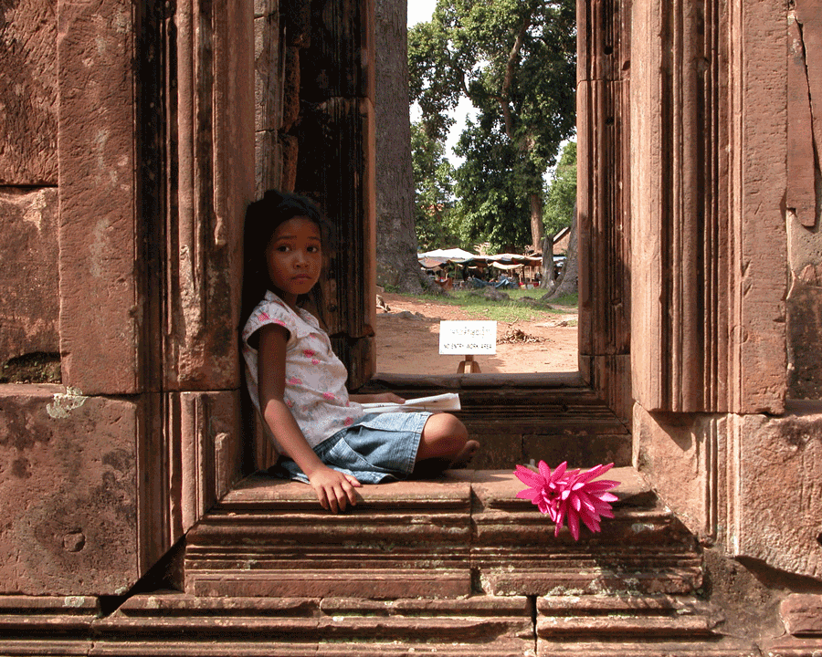 'Child Frame' © Naida Ginnane 2018 Nikon E5700. f/5, 1/180, ISO 100  Subtle, organic shapes and colours of the little girl and her flower contrast with the straight, horizontal and vertical lines in the red stone.