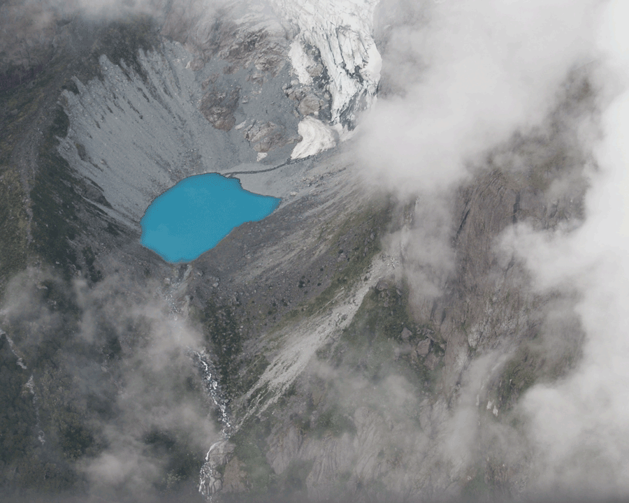 'Blue Lake' © 2011 Naida Ginnane Nikon D40 f/ 5.6, 1/125, ISO 100. This aerial view of a mountain lake features a stark contrast between the glacier blue of the lake and the barren grey mountainside around it.