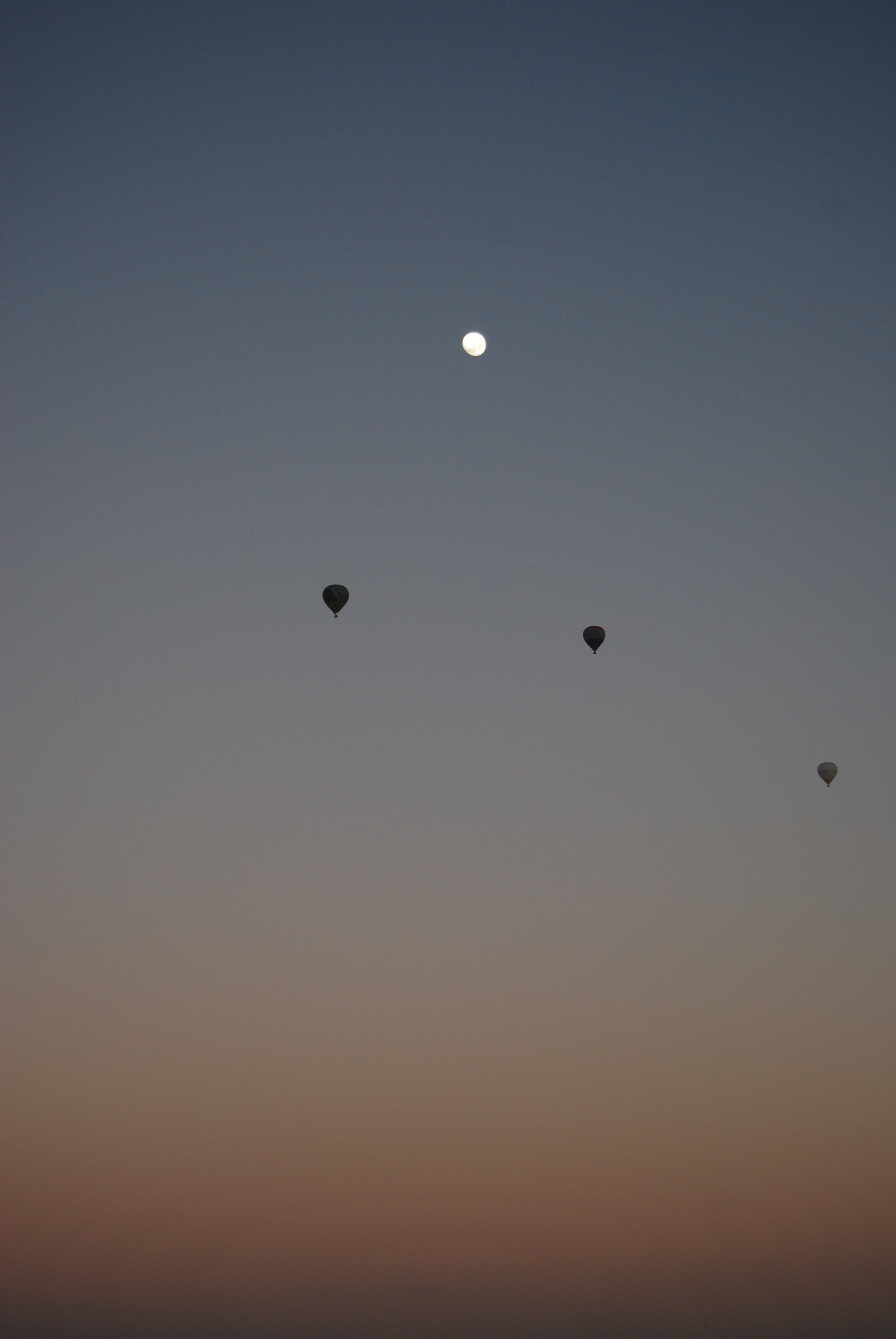'The Moon and Three Balloons' © Naida Ginnane 2010,Nikon D800, 24-70mm lens. f/5.3, 1/100, ISO 200. Subtle colours and very small shapes create a very peaceful and quiet moment in the early morning sky.