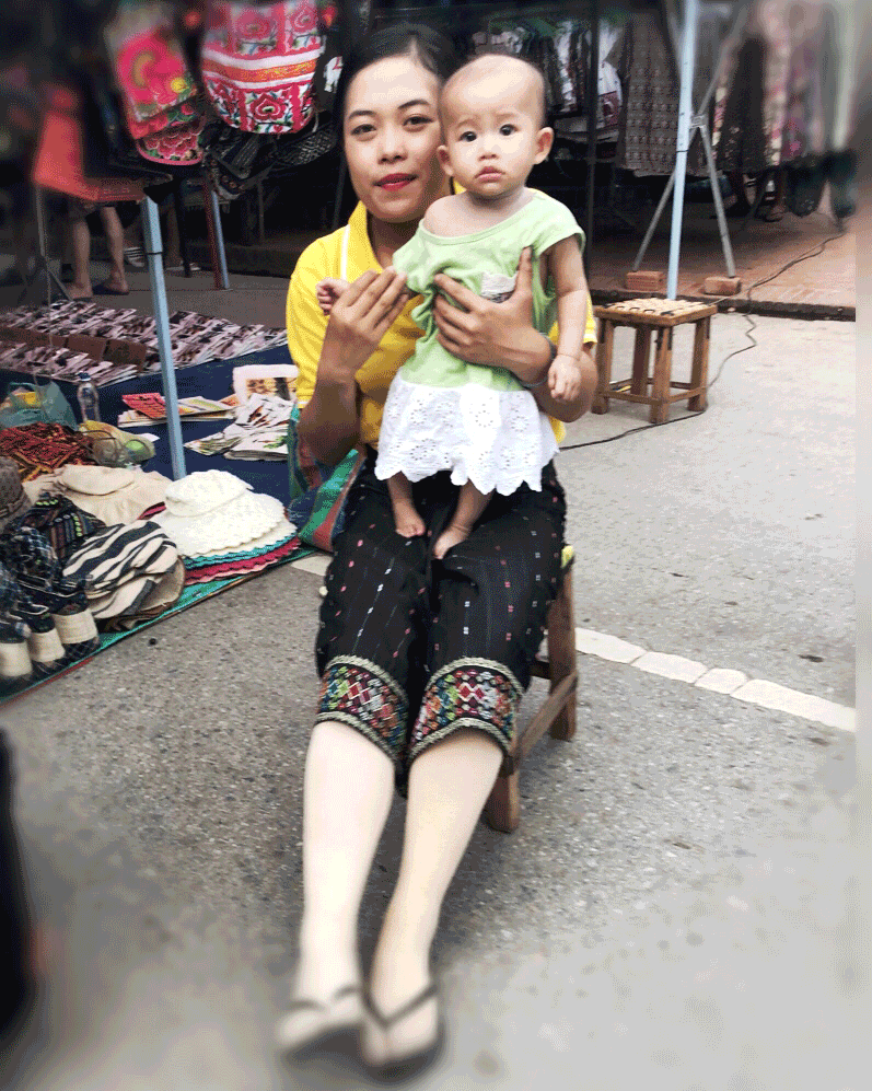 'Mother and Baby' © 2018 Naida Ginnane iPhone X. + Enlight App. A Laotian woman takes a moment from work to play with her baby daughter.