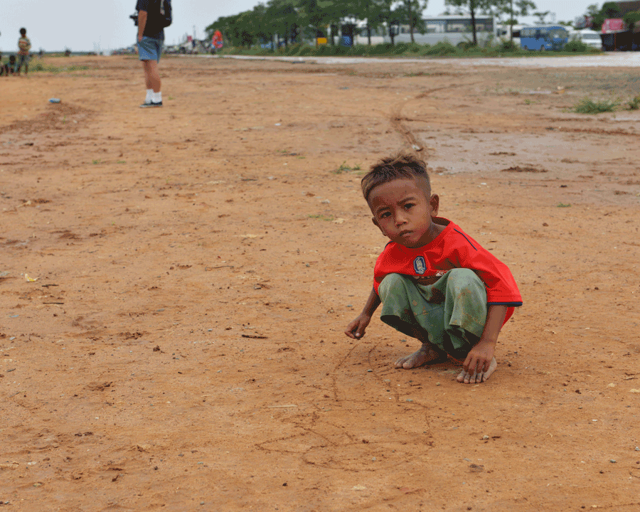 'Drawing' © Naida Ginnane 2016, Nikon D800 24-200mm lens 1/100, f/16, ISO 100. The low angle used to capture this child drawing in the dirt helps the viewer to engage with his world.