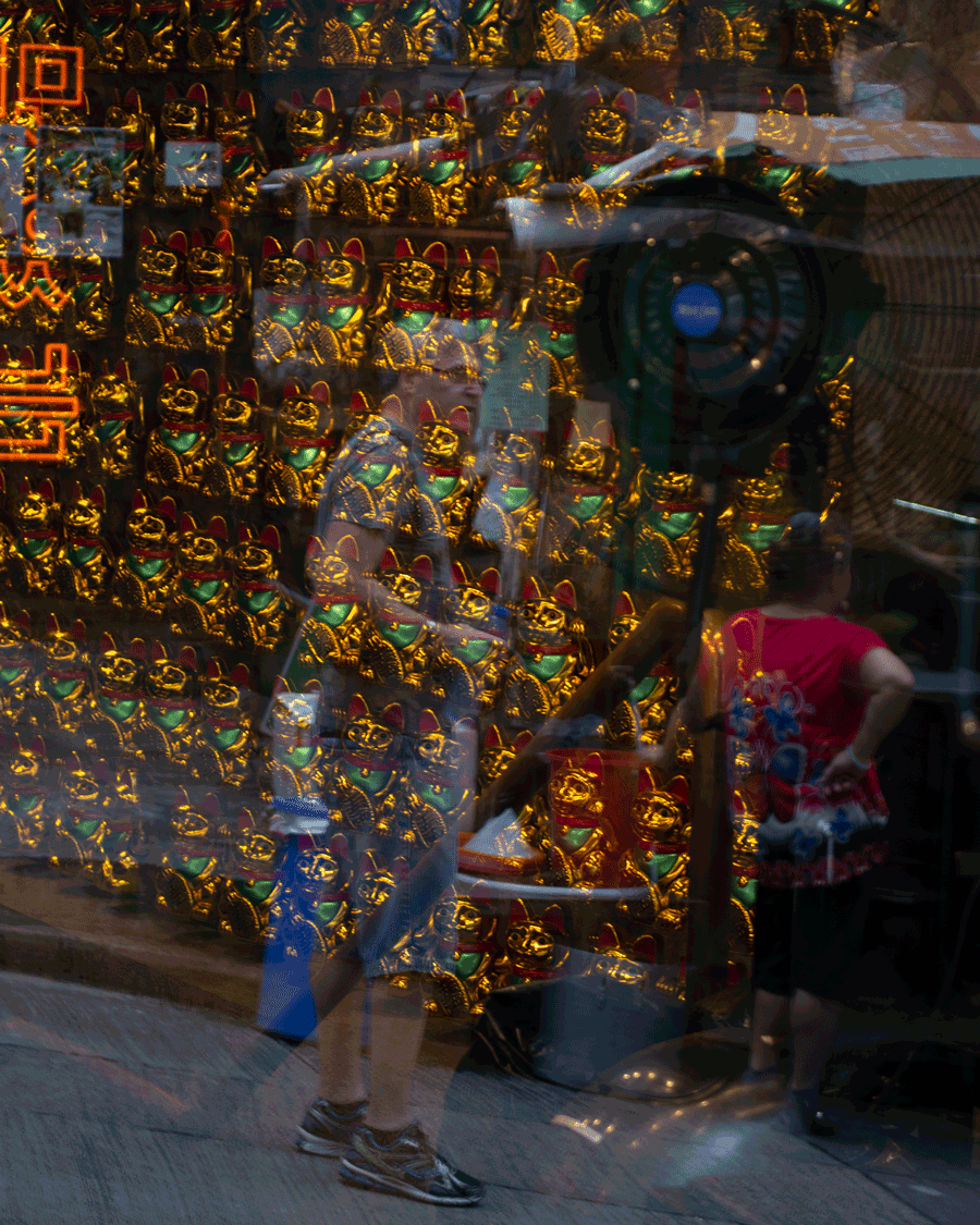 'Lost' © Naida Ginnane 2016, Nikon D800 24-200mm lens 1/100, f/16, ISO 100. I used the double reflections in shop windows to create a visually confusing scene, just like feeling lost. The figure is alone, partially visible amidst chaos, while another figure turns away suggesting no help is forthcoming.