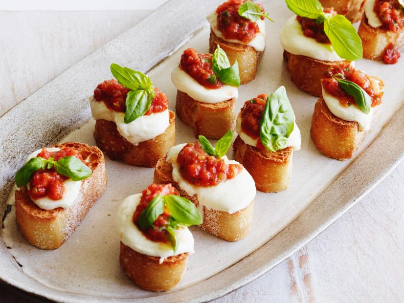 Tomato, Mozzarella & Basil Bruschetta - Ingredients:1 (32-ounce) can whole tomatoes, drained1 cup fresh basil leaves, washed and spun dry4 tablespoons extra-virgin olive oil6 cloves garlic, peeledKosher salt and freshly ground black pepper2 large French baquettes, sliced 1-inch thick (about 36 slices)1 1/2 pounds fresh mozzarella cheese, sliced 1/4-inch thickDirections:Preheat oven to 375 degrees F.In the bowl of a food processor, add drained tomatoes, 1 cup basil leaves, olive oil and 2 cloves garlic. Pulse until smooth, but somewhat chunky. Season with salt and pepper.On a baking sheet, line up baguette slices. Toast in oven for about 3 minutes or until light golden brown. Working quickly, rub the remaining garlic on the toasted side of each slice and then lay a piece of mozzarella cheese on top. Place bread back in oven and melt cheese slightly, about 45 seconds. Remove from oven and spread one tablespoon of the tomato mixture on each piece.Place bruschetta on decorative platter and garnish with basil leaves.foodnetwork.com