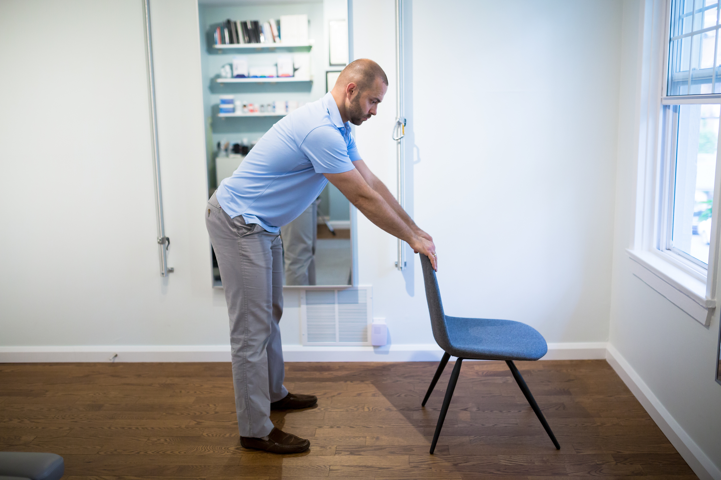 STEP 1:  Start by standing about one full arm length away from a chair. Place your hands on the chair with your feet hip width apart.