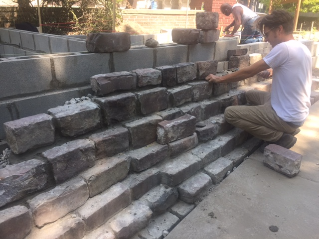 Architect Anthony Morin lays stone sourced and upcycled from one of Detroit's first paved streets, Atwater Street.