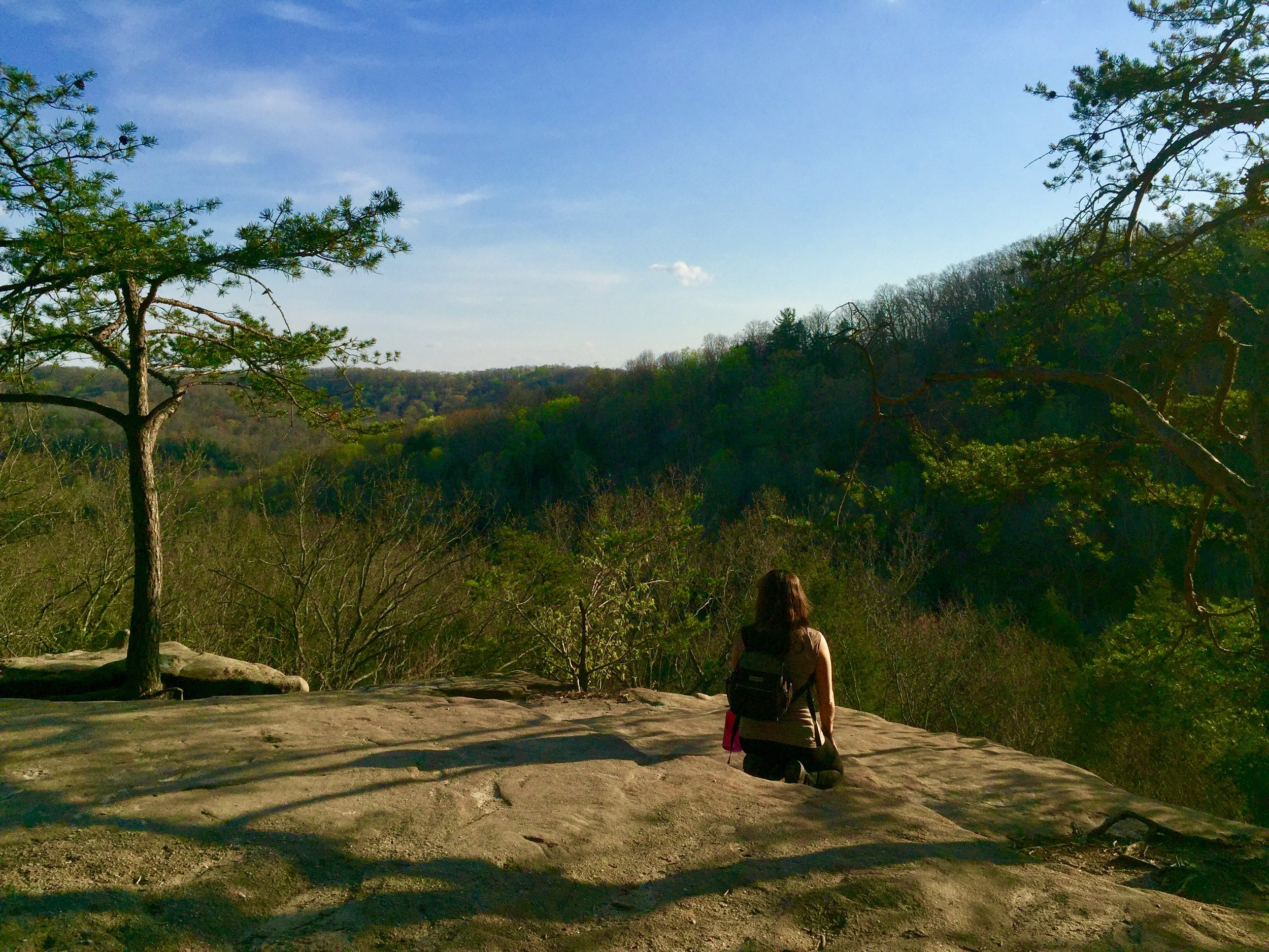 Dianna Guldi   sitting on a ledge in Hocking Hills.