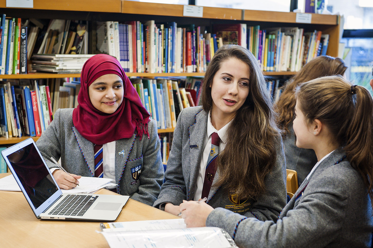 Girls working together in library with notebook computer
