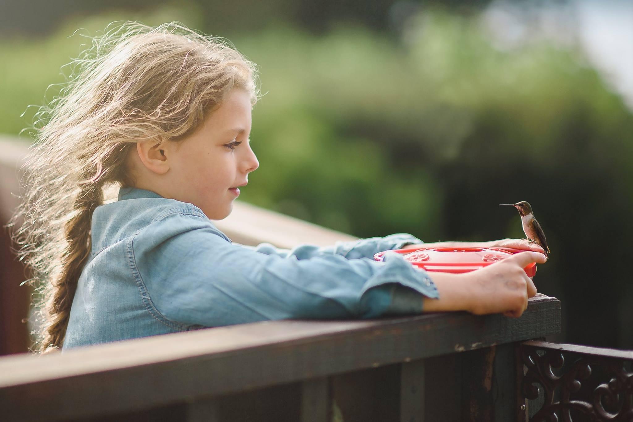 little girl holds hummingbird