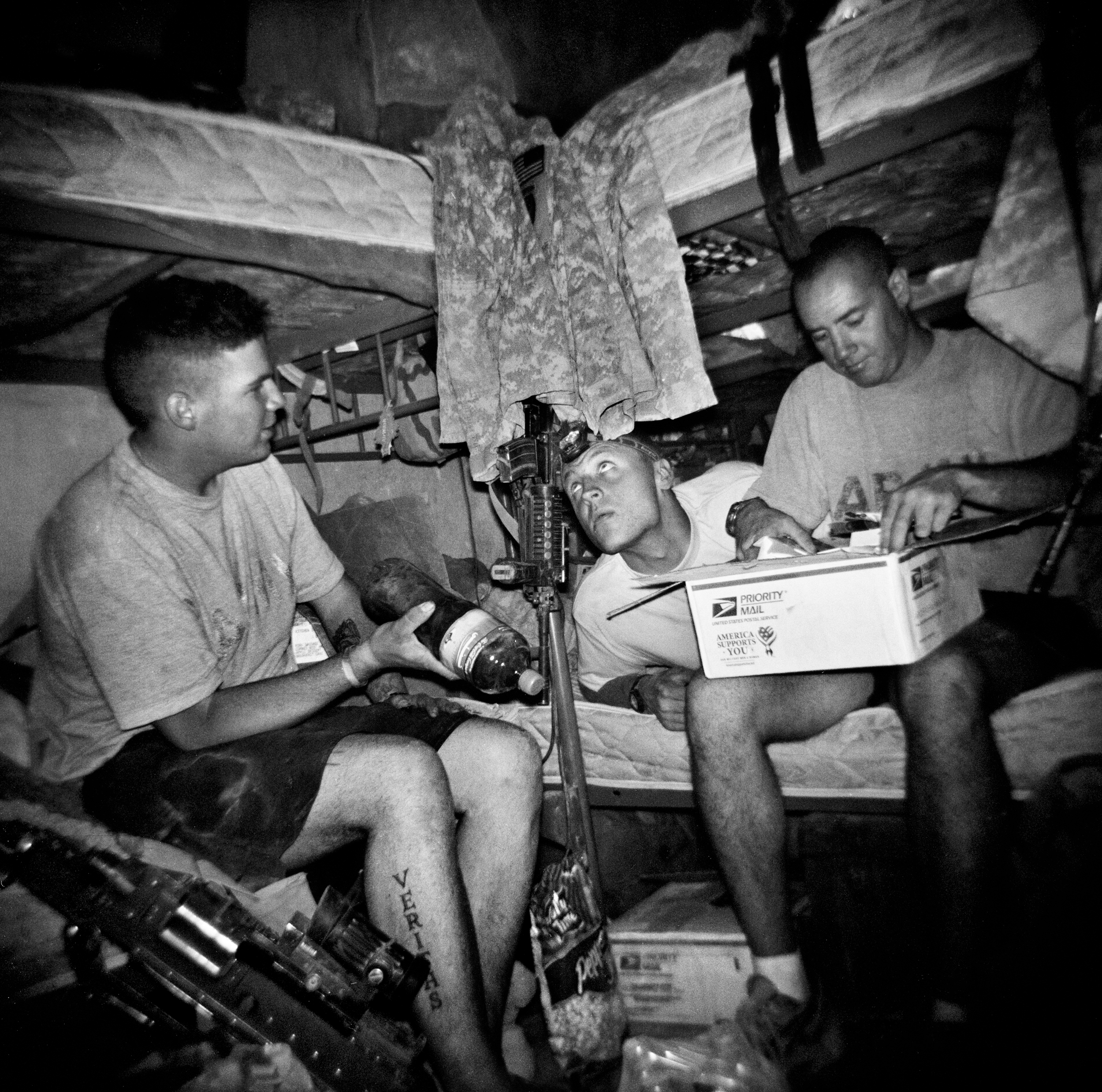 SPC Adam Ramsey, SPC Aldin Zukic, and SPC Jason Vann open mail and care packages at COP Charkh in Logar Province.
