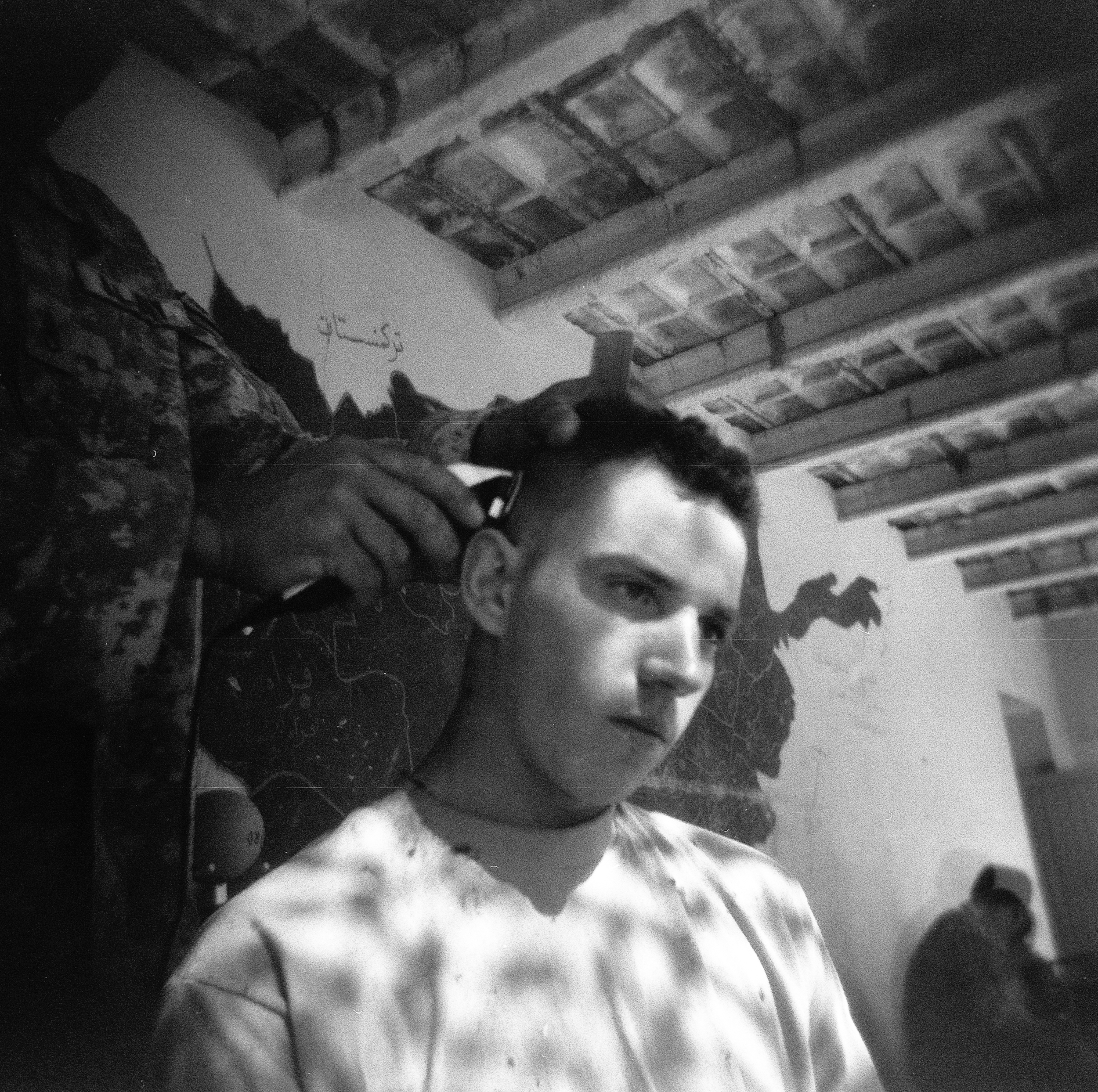PFC Michael Mackey gets his hair cut at COP Charkh in Logar Province.