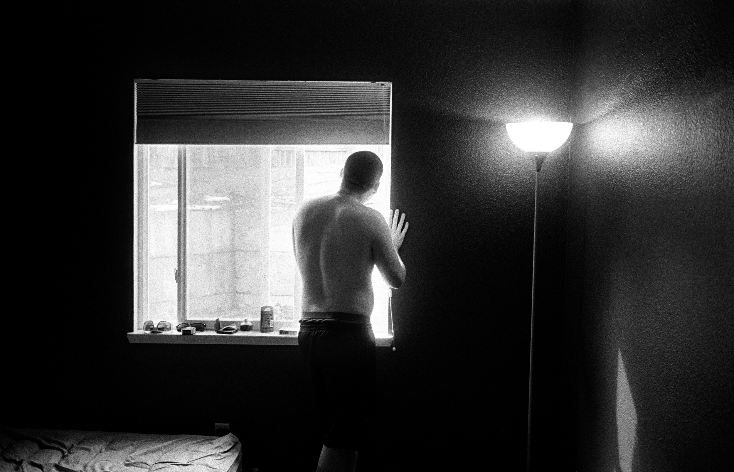 SPC Adam Ramsey, 22, looks out the bedroom window as he experience a psychotic episode in Carson City, Nevada, 2010. Ramsey served 12 months as a 240 machine gunner in Afghanistan. After returning home he became severely depression and began having psychosis and and suicidal thoughts.