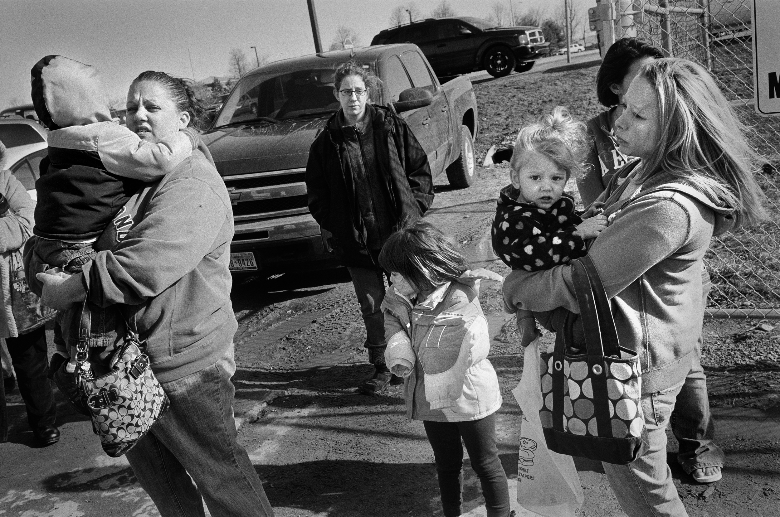 Wives and their children watch their husbands leave for Afghanistan at Fort Drum, New York, 2011.