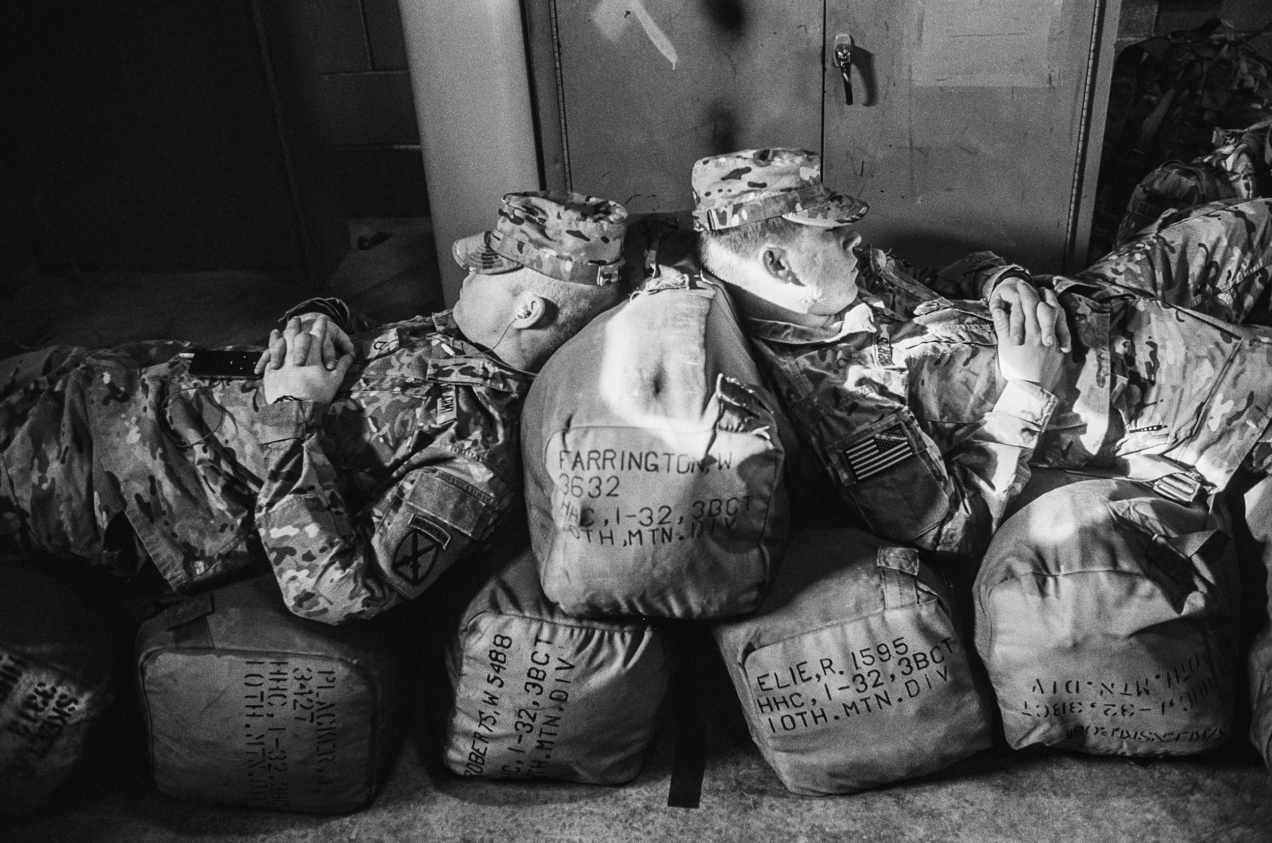 Two soldiers naps on their duffle bags before deploying to Afghanistan at Fort Drum, New York, 2011.