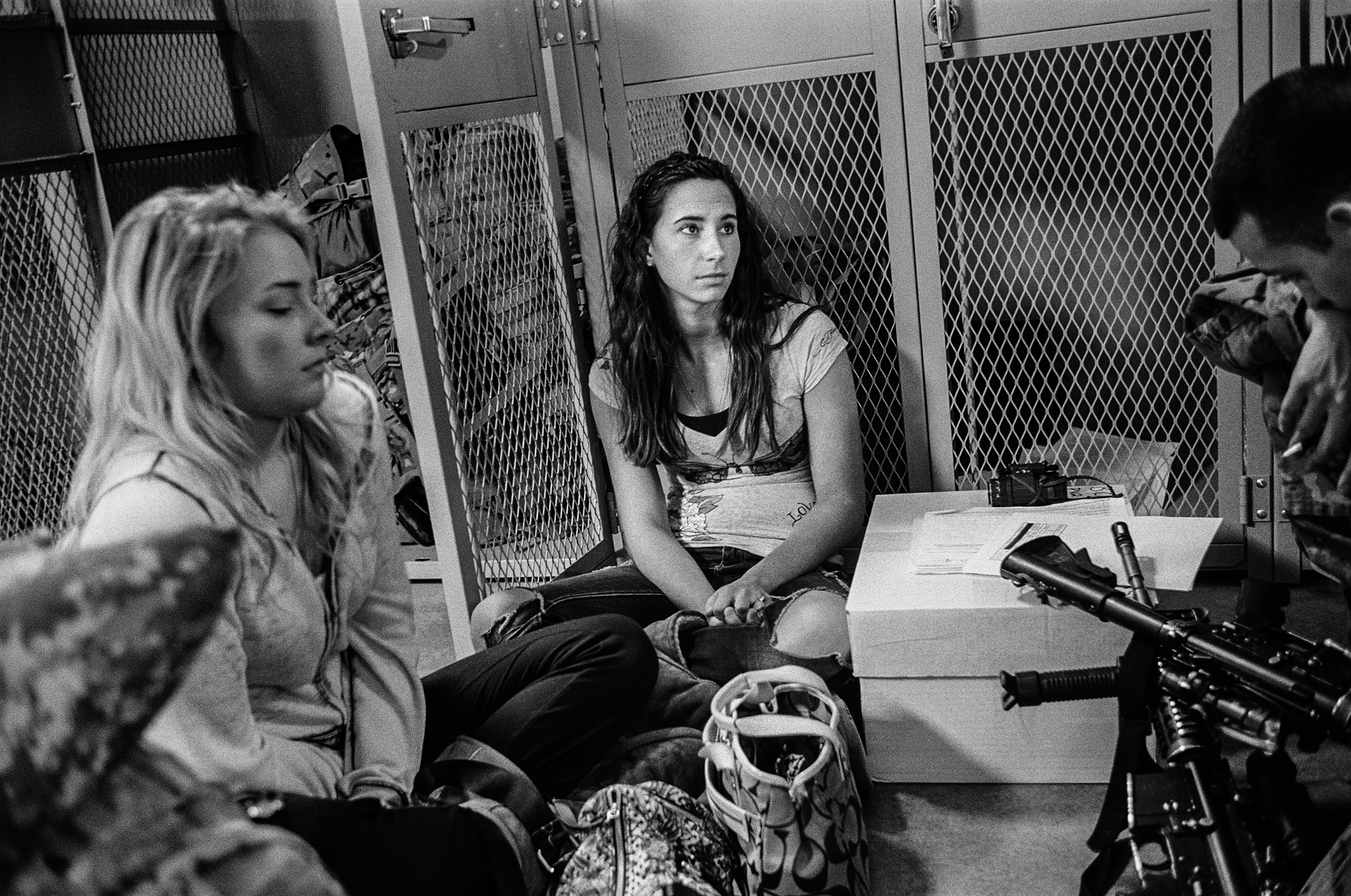 A young woman sits quietly in a locker room before her boyfriend deploys to Afghanistan at Fort Drum, New York, 2011.