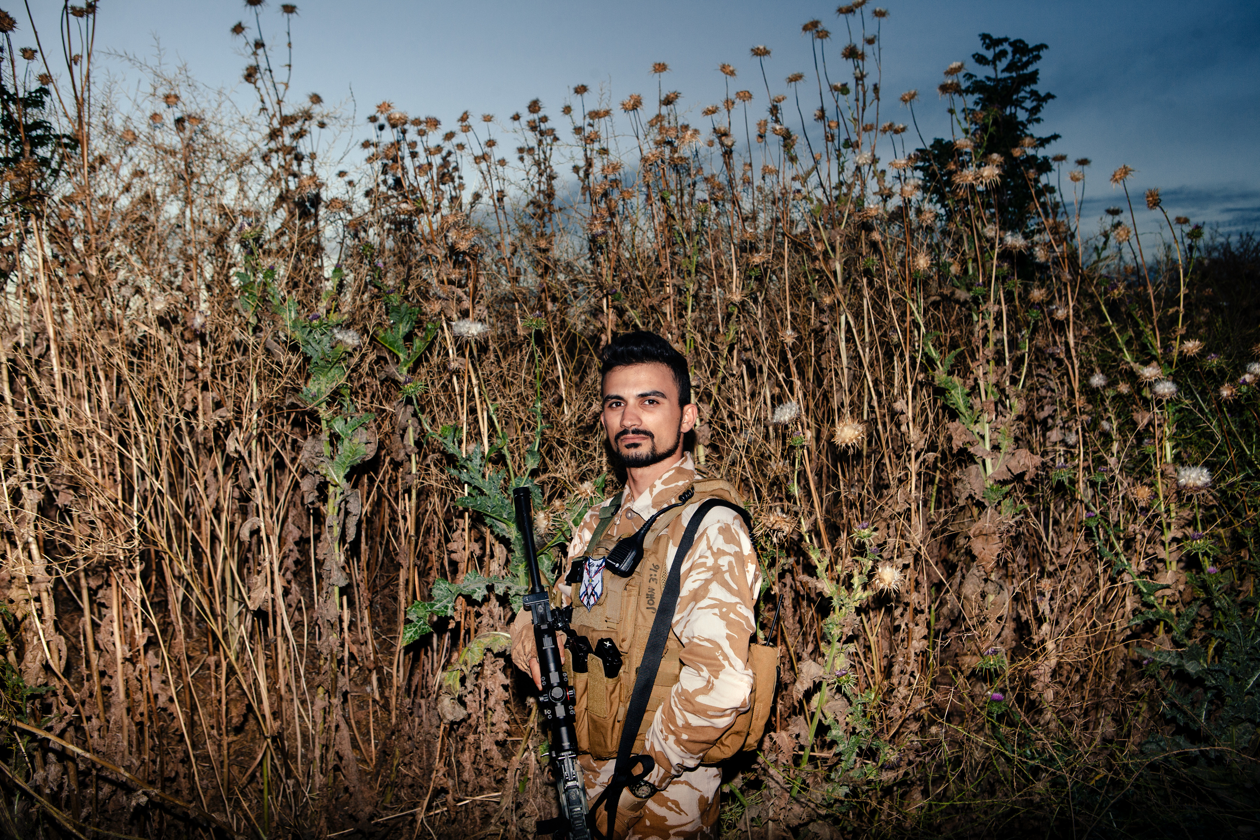 "Dwekh Nawsha soldier Marcus Nissan poses for a portrait in Baqofah, Ninevah Province, Iraq. The Dwekh Nawsha (in Syriac ""one who sacrifices"") is a military organization created in mid-2014 to defend Iraq's Assyrian Christians from ISIS, and possibly retake their lands currently controlled by ISIS."