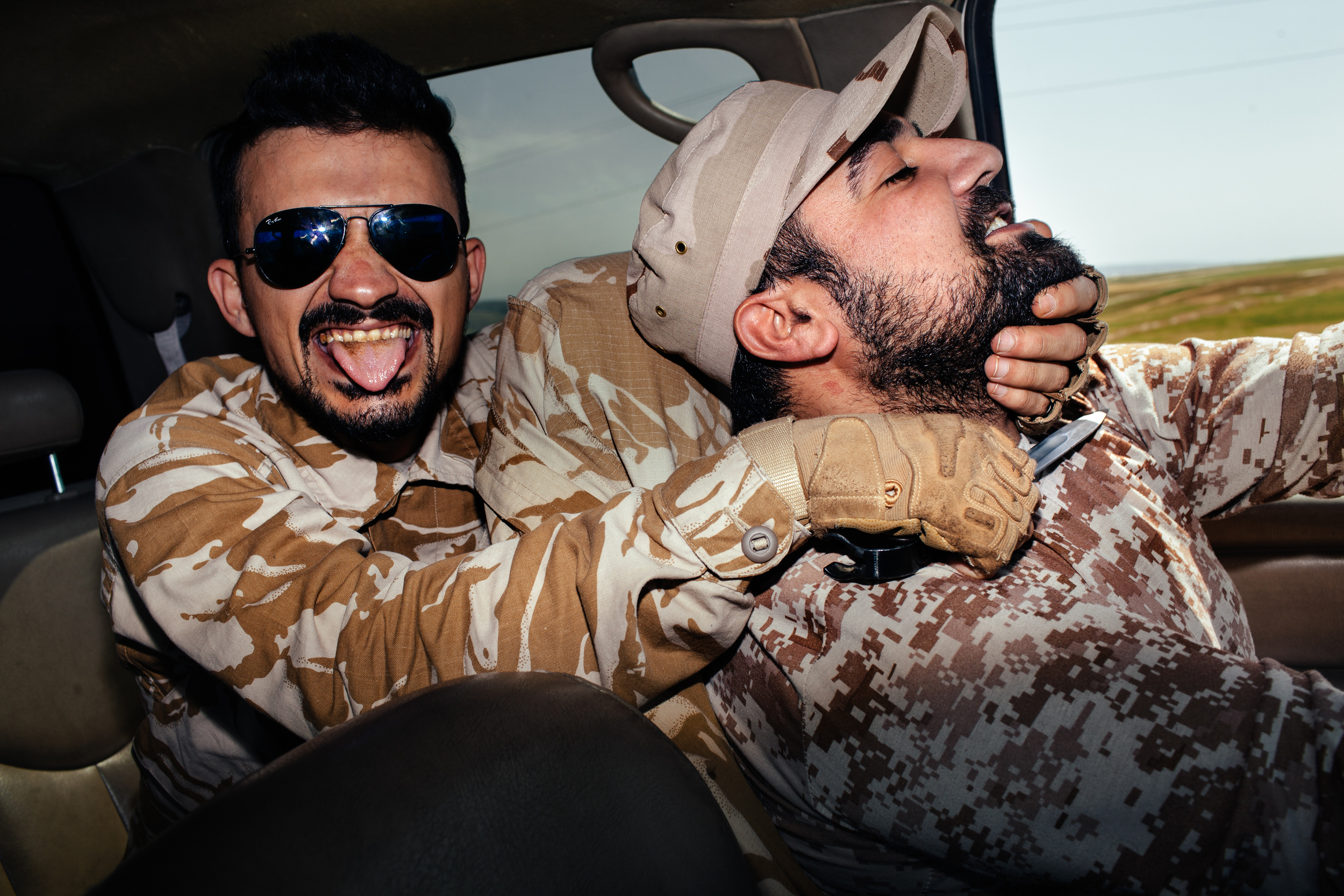 Dwekh Nawsha soldier Marcus Nissan jokes around with a fellow soldier while driving to their unit's base in Baqofa, Northern Iraqi Kurdistan.