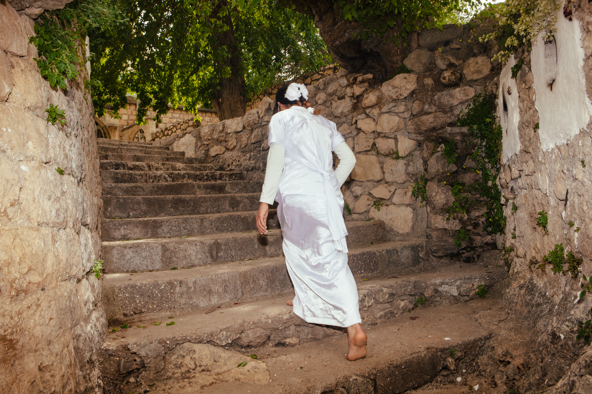 Sundis Ziad Hassan wears a white gown, a Yezidi tradition, as she walks to pray at the Lalish temple, the most sacred and only Yezidi temple in the world, Northern Iraqi Kurdistan.