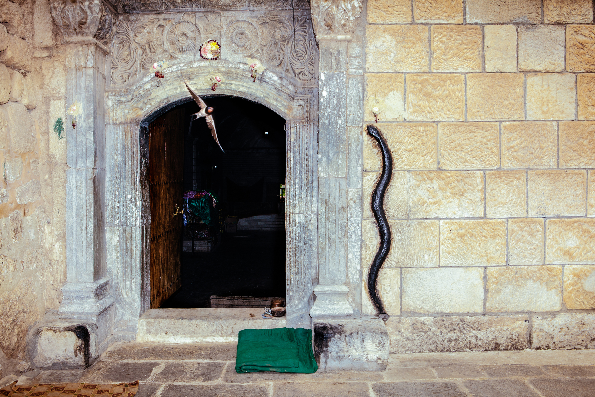 A bird flies out of Lalish temple which features a stone black snake on it's wall in Northern Iraqi Kurdistan. Lalish is the most sacred and only Yezidi temple in the world. According to legend, the snake was once a live serpent but was transformed it into a solid fixture by Sheikh Adi when it attempted to scale the wall of the temple.