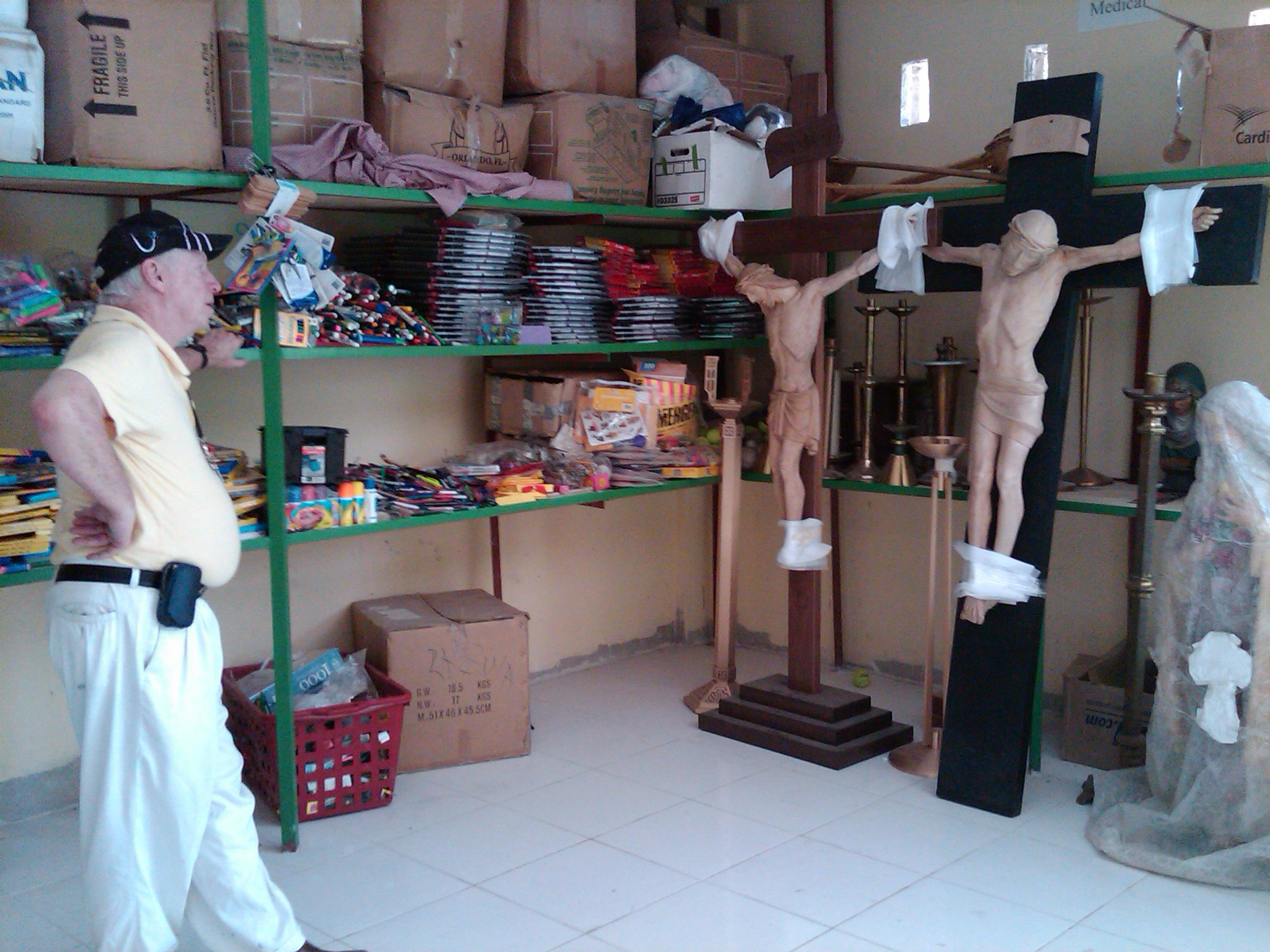 Fr. Tom in looks at donated crosses in our depot