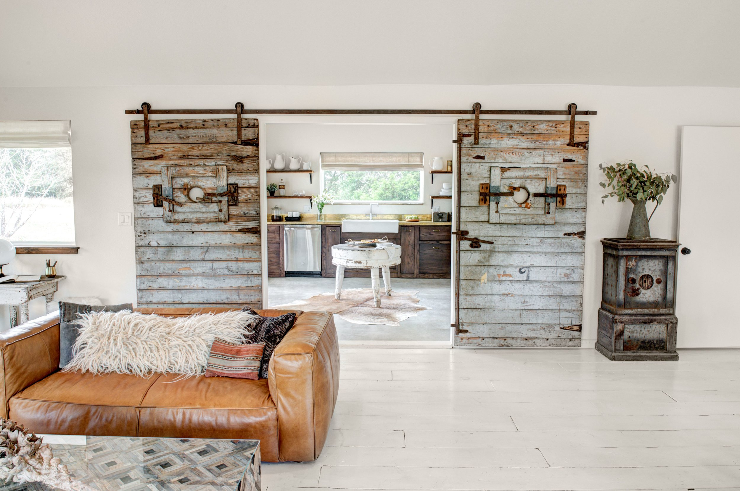 Reclaimed cotton gin doors separate the Boho kitchen from the great room.