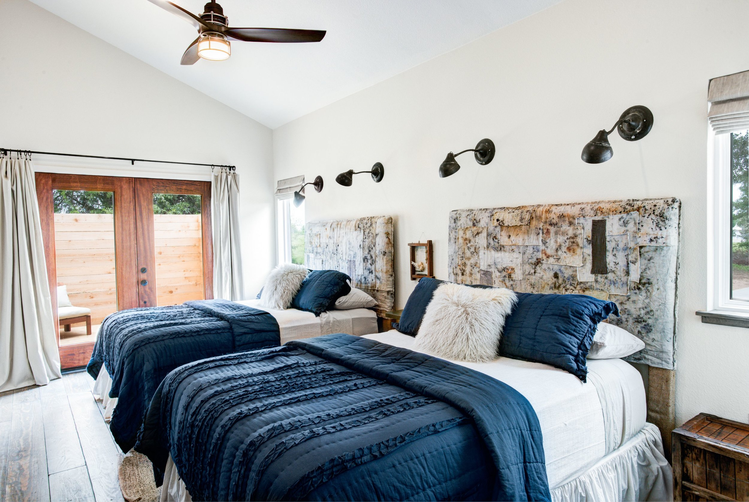 The Boho guest bedroom features two queen-sized bed, ensuite full bath with soaking tub and shower, and a private ensuite patio.