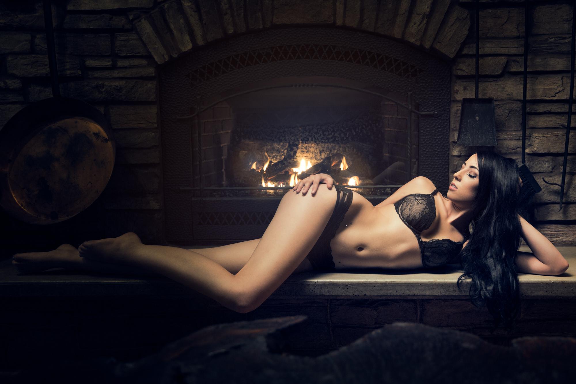 tasteful boudoir photography of Vanessa near a fireplace.