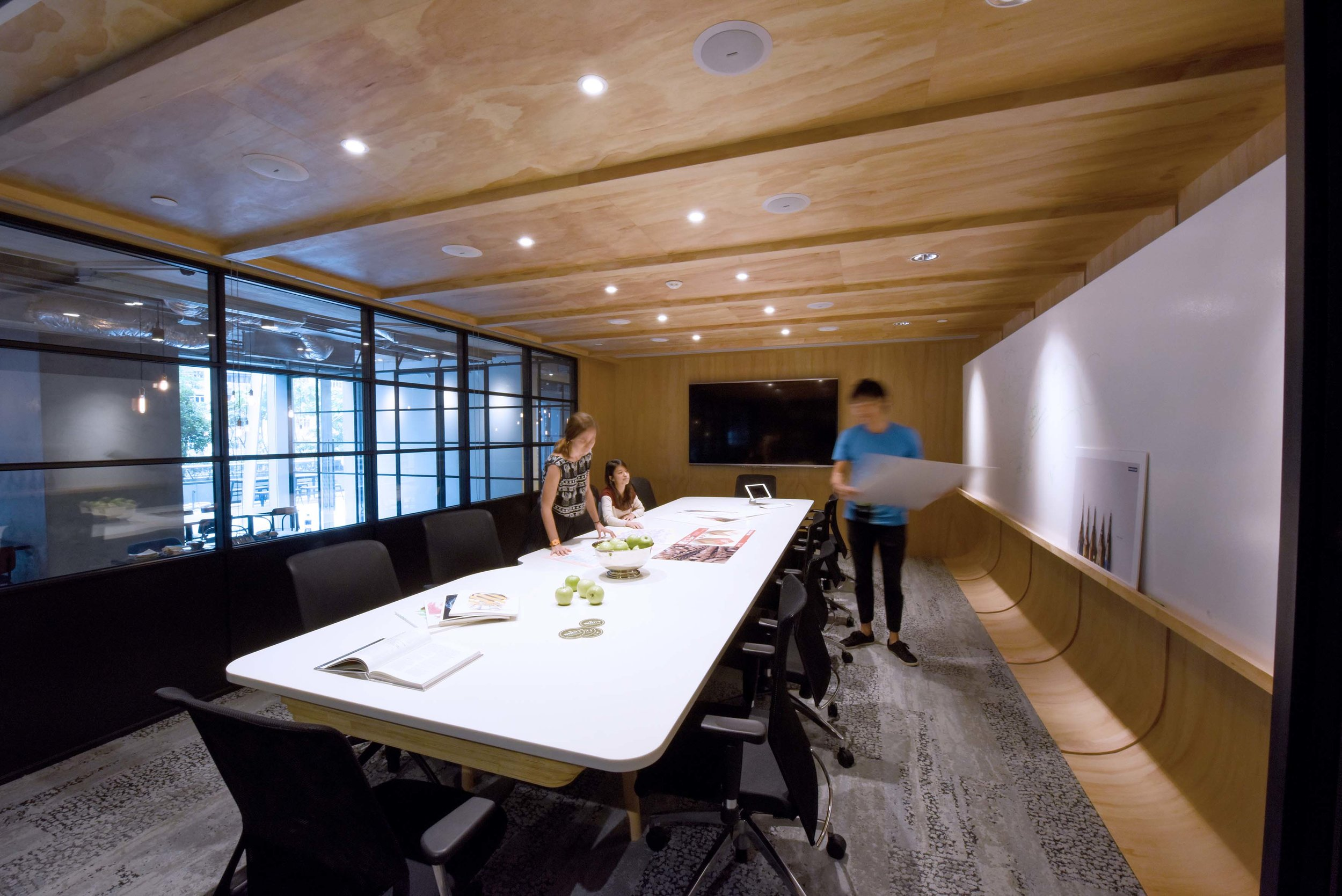 The bespoke CNC milled meeting tables inside were uniquely designed using layers of plywood and corian to house all AV equipment.