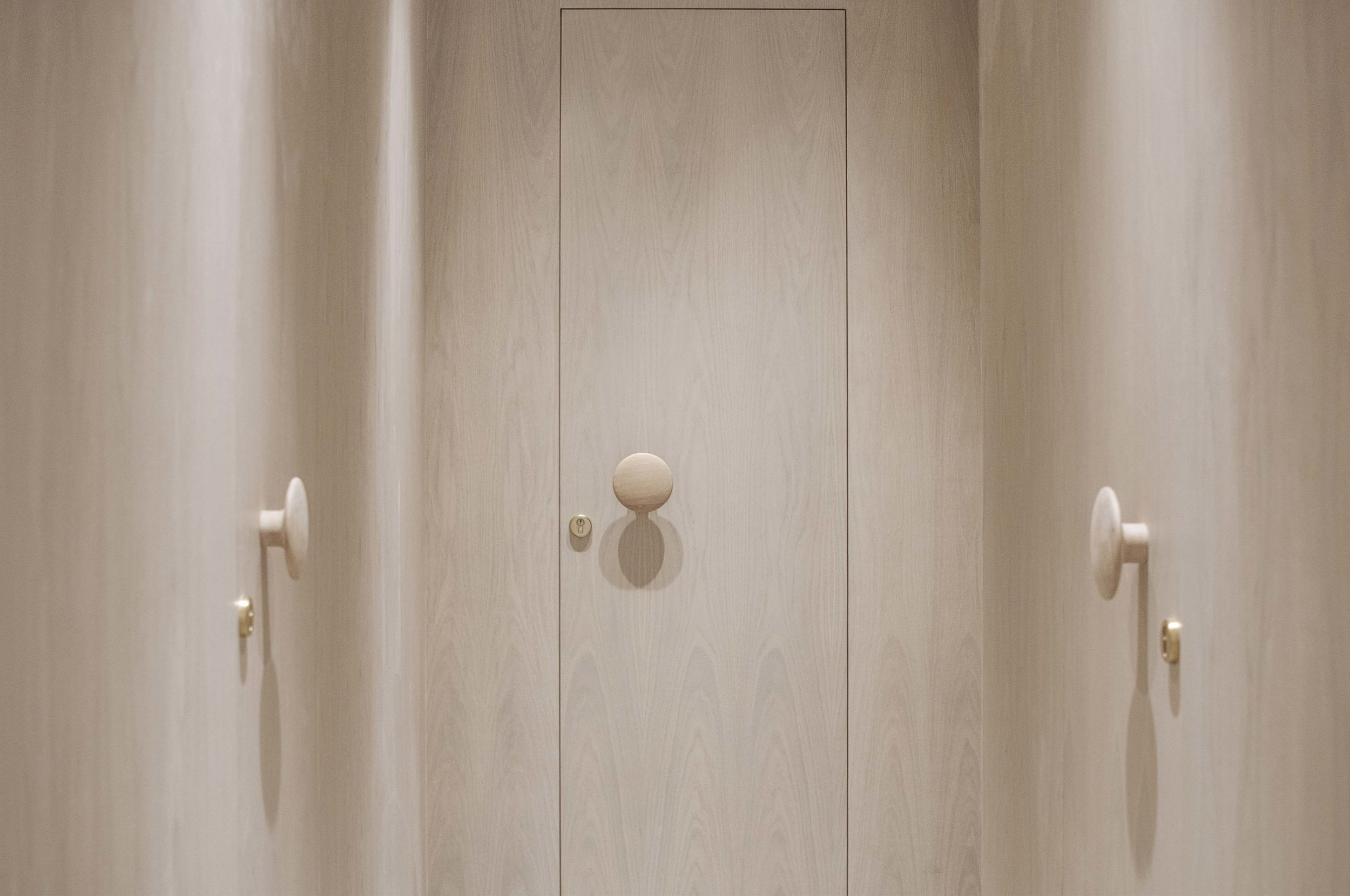 The private spaces are considered as 'small studio apartments' within the big apartment. A timber lined corridor differentiates the private quarters, with concealed doors to the private bedrooms suites.
