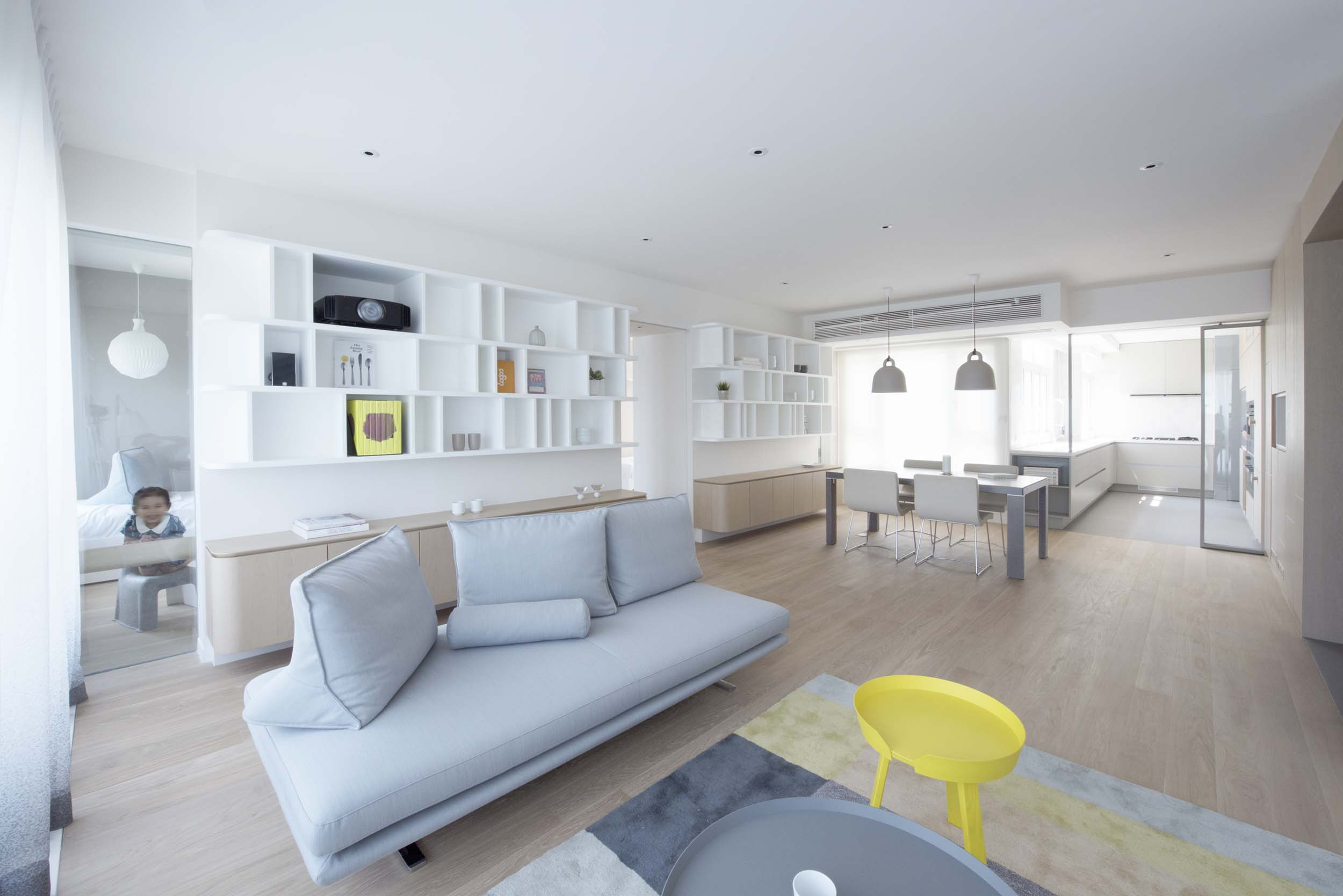 A long slithering wooden wall connects living spaces and kitchen together, while providing plenty of concealed storages, appliances and display niches. The resulting spaces are open, airy and light – with a large feature bookshelf that appears to be floating. Daylight and ocean views are extended by strategically positioned mirrors and glass partitions, anchoring the apartment in its beautiful surroundings.