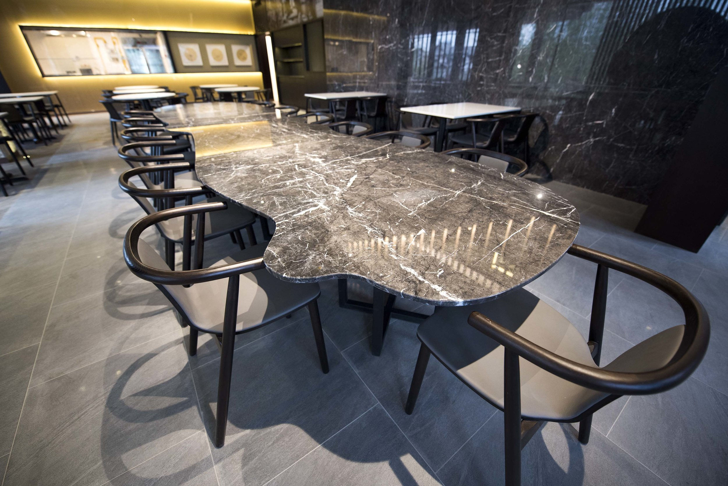 Inspired by traditional Chinese garden rock art, this impressive 4.8m long marble table installation is full of playful curves and appears to be floating. It functions as a dynamic 18 person sharing table for multipurpose events.