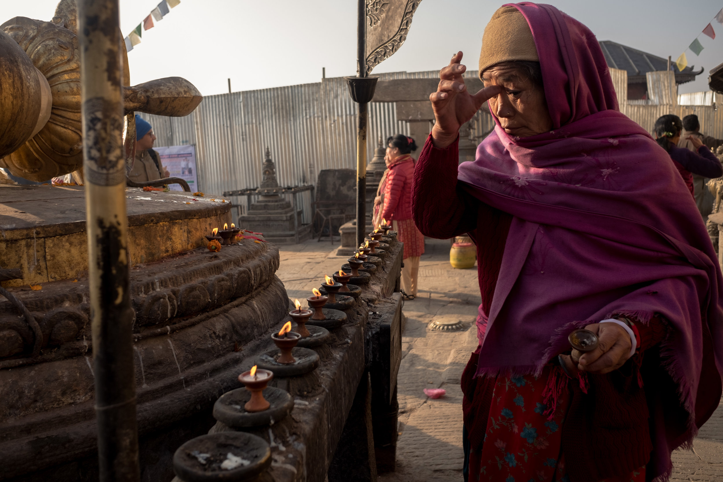 A lady touching her forehead in Swayabhunath.