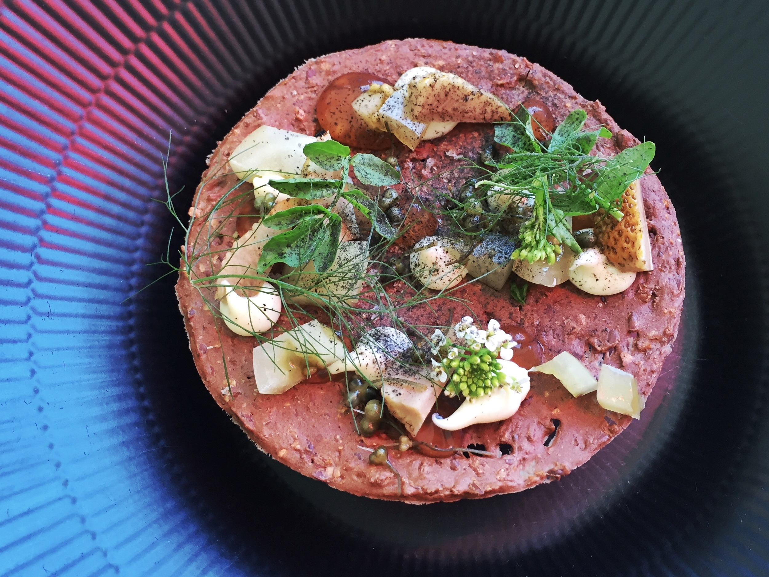 Foie gras underneath a rye cracker topped with green strawberries and an assortment of herbs.