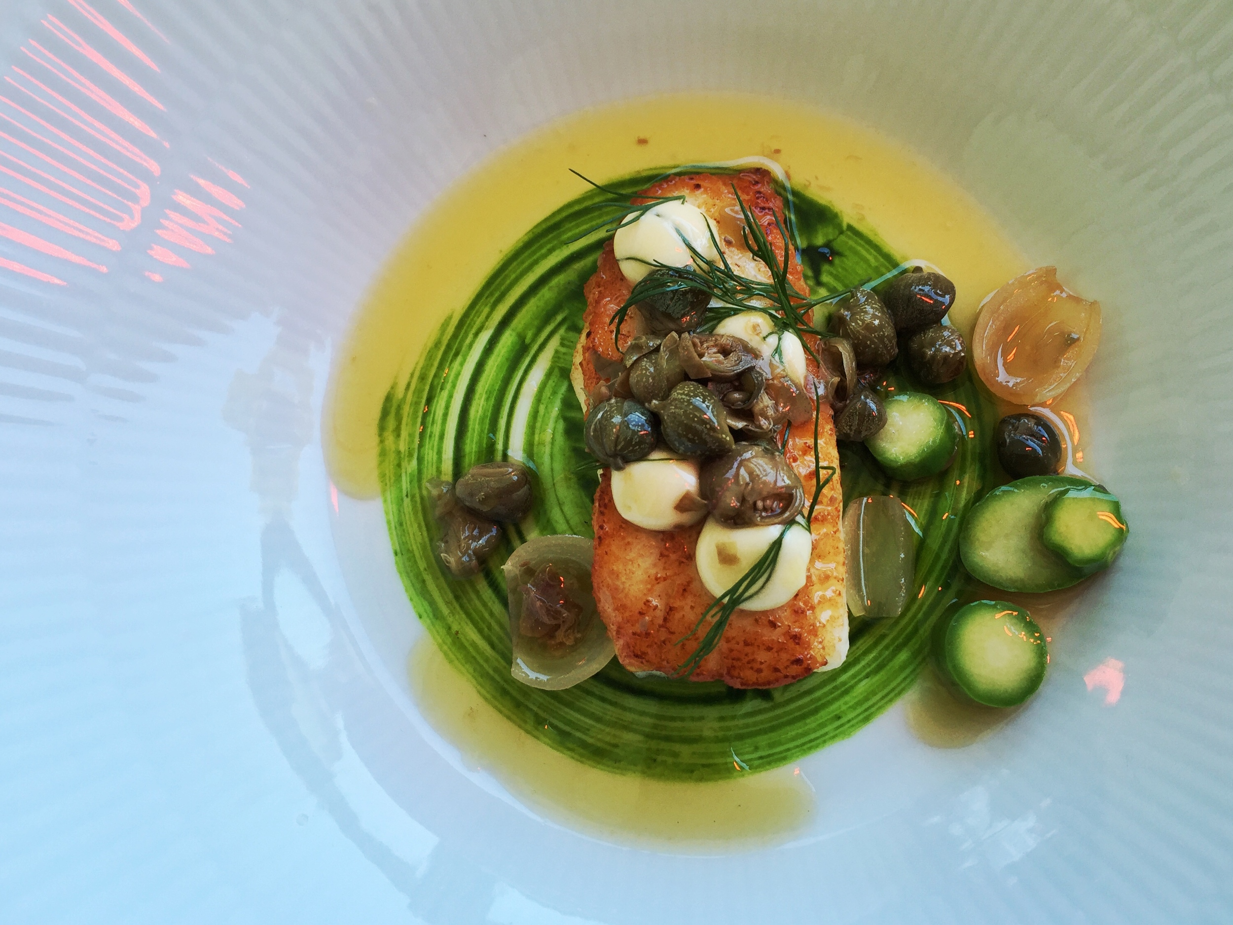 Poached black cod with vegetables.