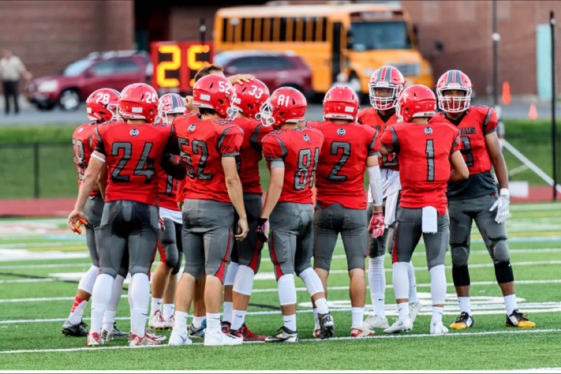 Members of the Jamesville-DeWitt High School Varsity Football team gather in a huddle before a home game