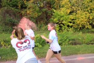 J-D Students run through a handful of colored powder on their way to the finish line