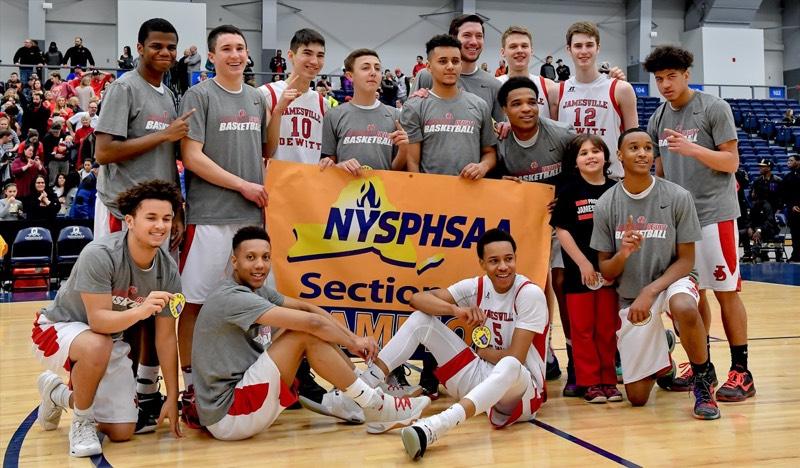 The Jamesville-DeWitt Varsity Boys Basketball team celebrates their Section III Championship win over Syracuse Academy of Science.