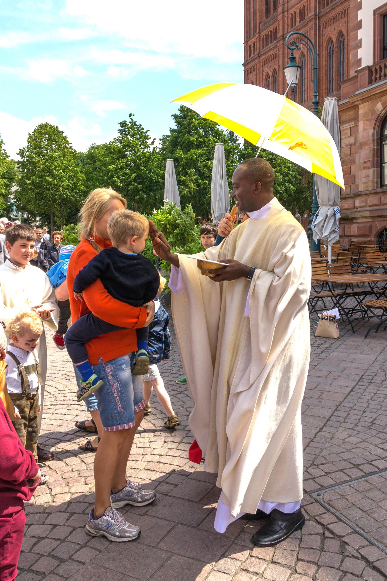 Pfarrer Jude Okeke segnet ein Kind bei der Kommunion der Fronleichnamsmesse. Foto: 2014 Benjamin Dahlhoff