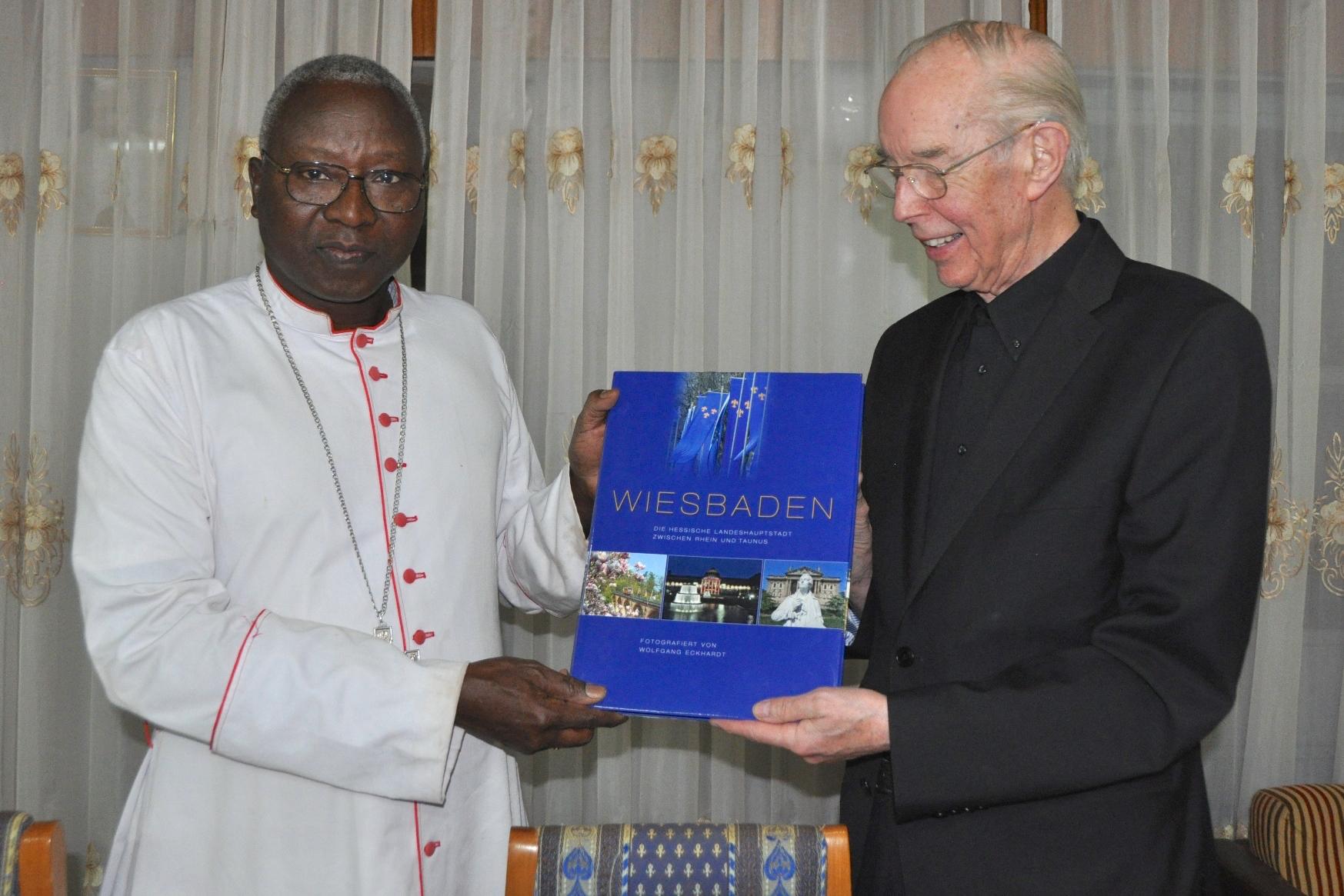 """Das Foto zeigt Kardinal Philippe Ouedraogo mit Pfarrer Werner Bardenhewer im Januar 2016 in Burkina Faso bei der Überreichung eines """"Wiesbaden-Bildbandes""""."""