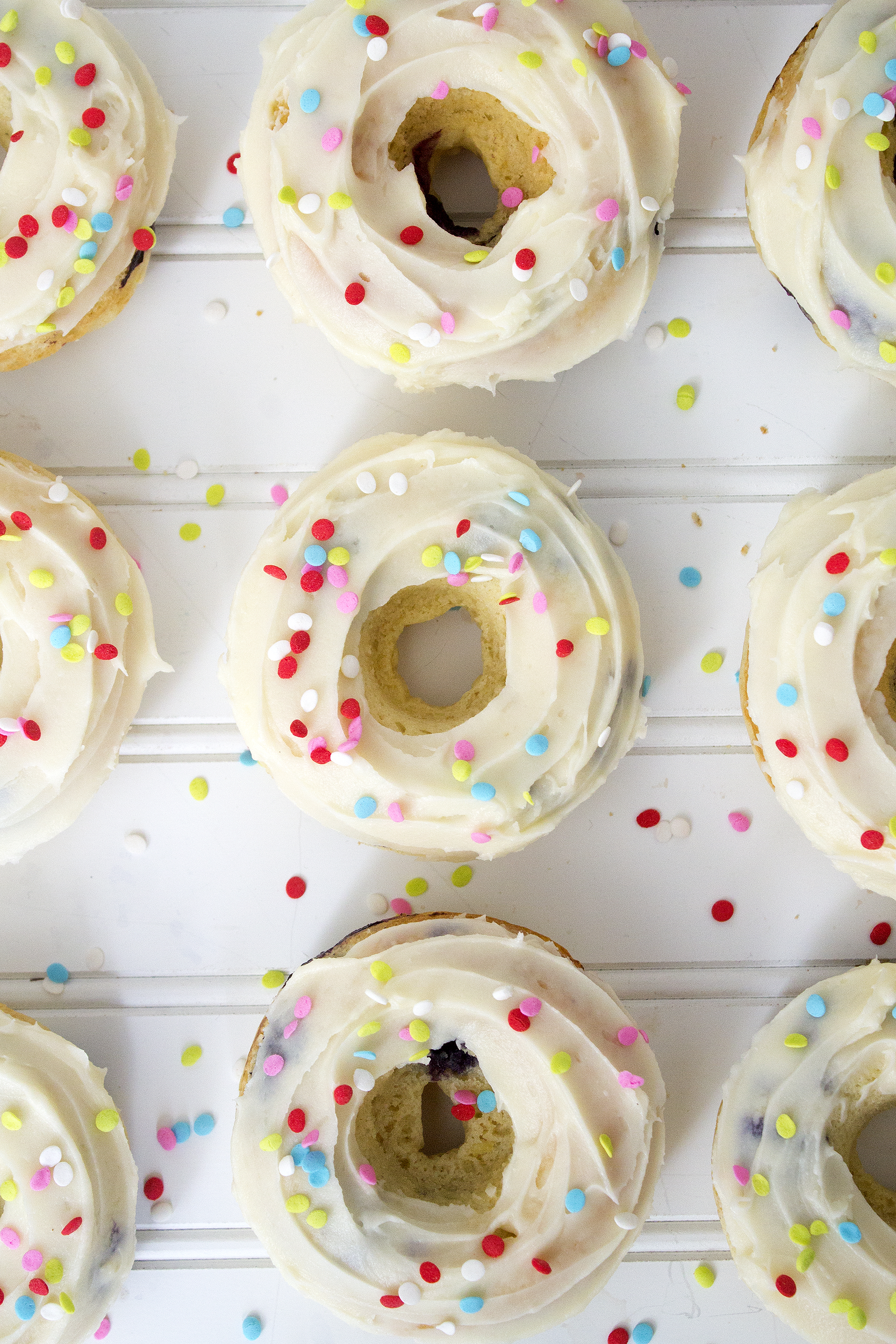 Sprinkles make everything better! Get the recipe for these Blueberry and Lemon Donuts topped with Cream Cheese Frosting. Unusuallylovely.com
