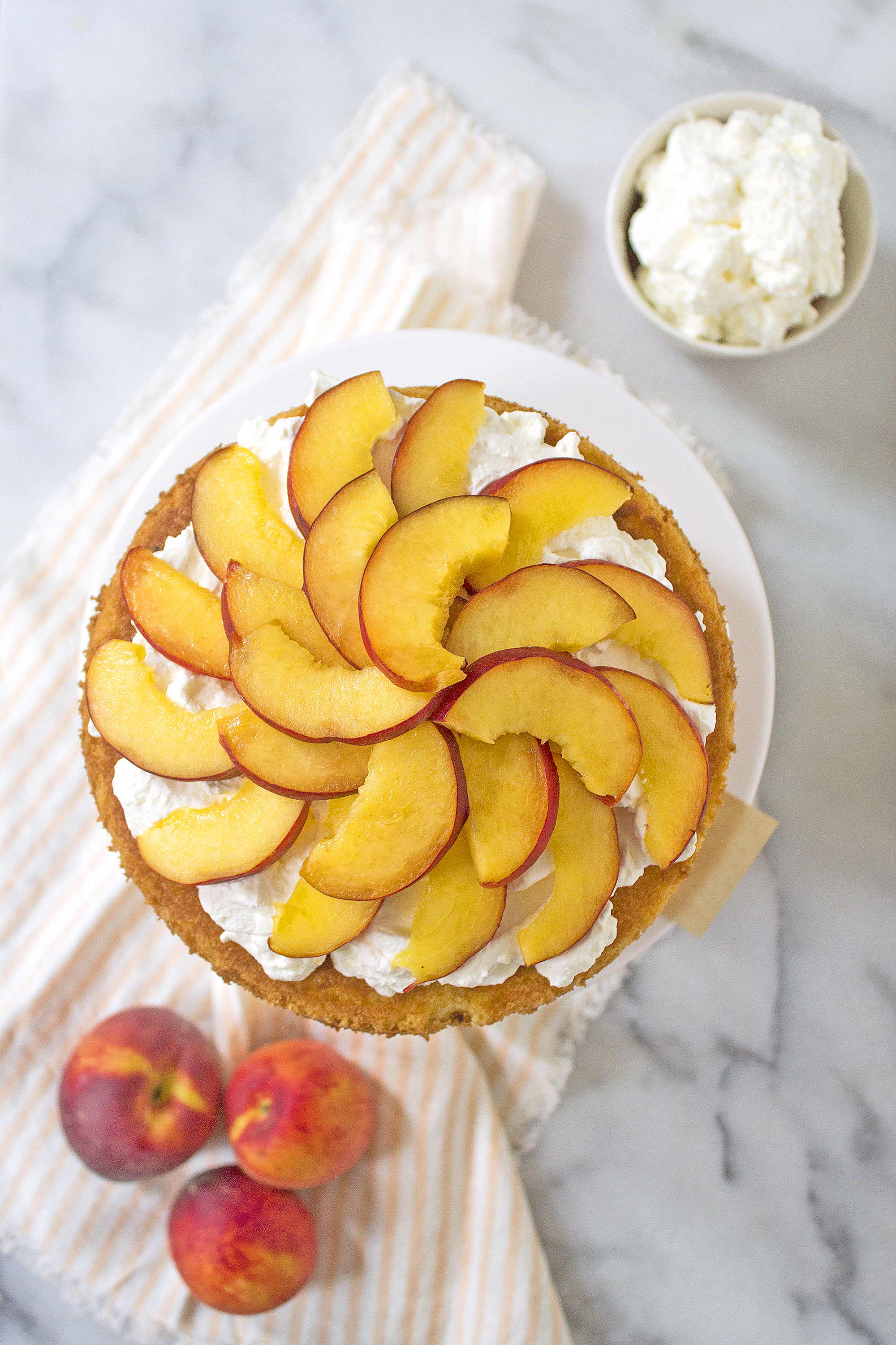 The perfect summer shortcake topped with fresh peaches and homemade whipped cream. Get the recipe: unusuallylovely.com