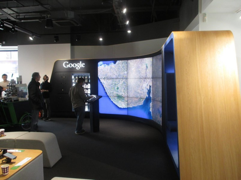 Curved video wall (showing Google Earth), controlled by an interactive pad