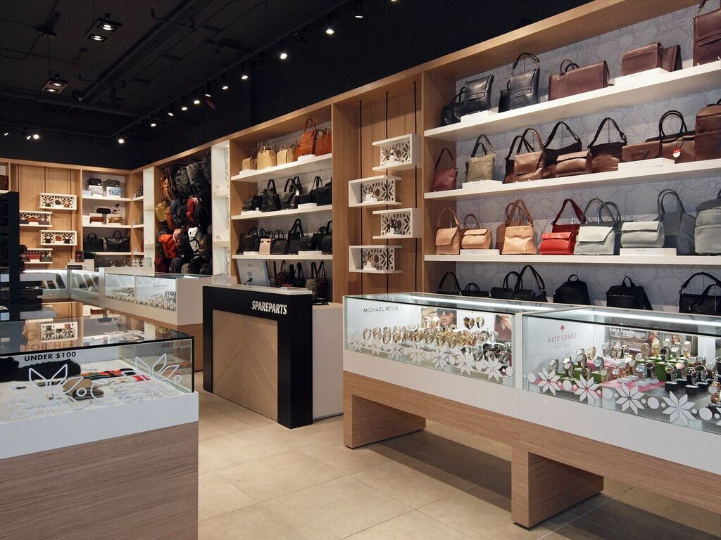 Cash desk at centre, with displays for handbags, watches and other accessories. Photo:  Peregrine.Build
