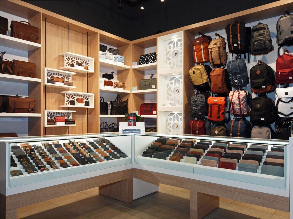 Backpacks, wallets and other product displayed on walls and in glass-enclosed cases. Photo:  Peregrine.Build
