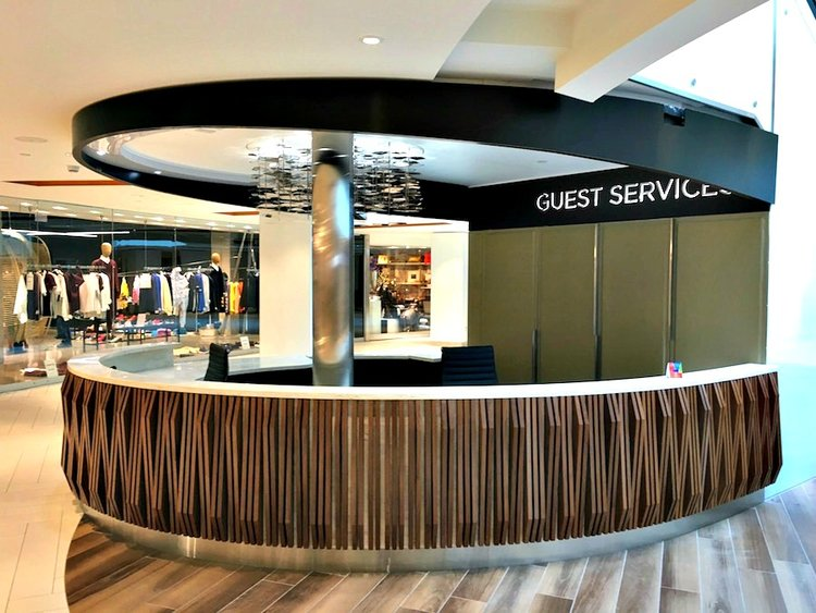 (an ELEGANTLY shaped and welcoming guest services desk at Yorkville Village in Toronto. Photo: First Capital Realty)