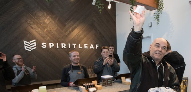 A customer holds up his receipt after being the first person to buy cannabis at the SpiritLeaf cannabis store in Kingston, Ont., on April 1, 2019. THE CANADIAN PRESS/Lars Hagberg